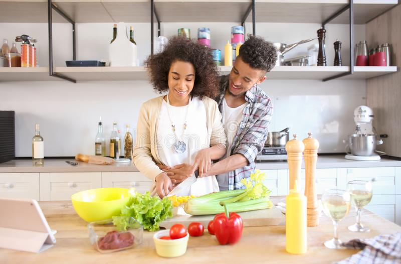 Young African-American couple cooking together in kitchen stock image