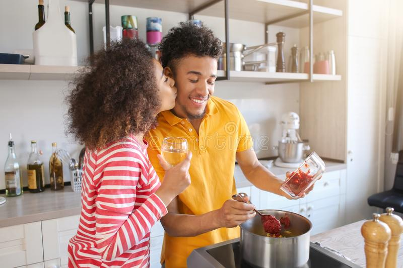 Young African-American couple cooking together in kitchen royalty free stock photos