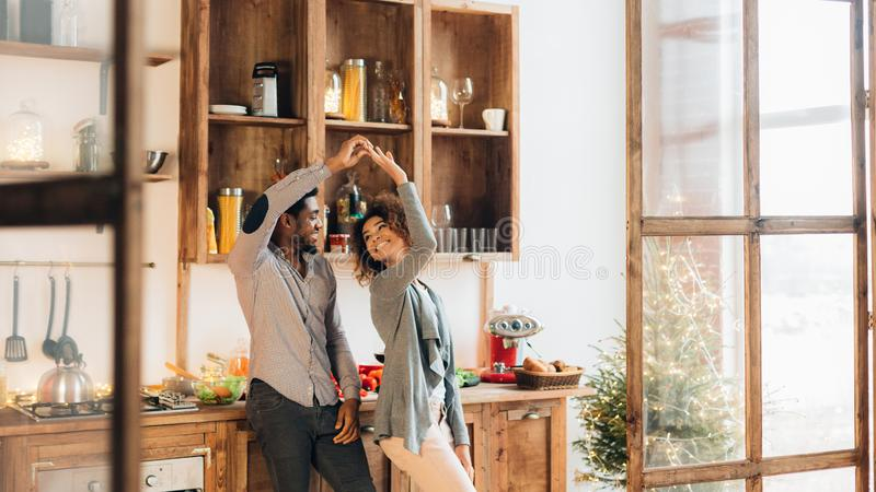 Young african-american couple dancing in kitchen, copy space stock photos