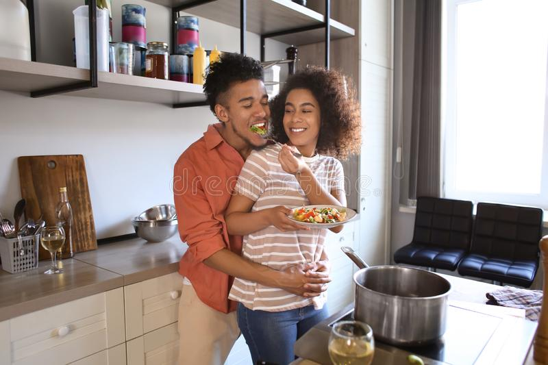 Young African-American couple hugging and tasting food in kitchen royalty free stock photos