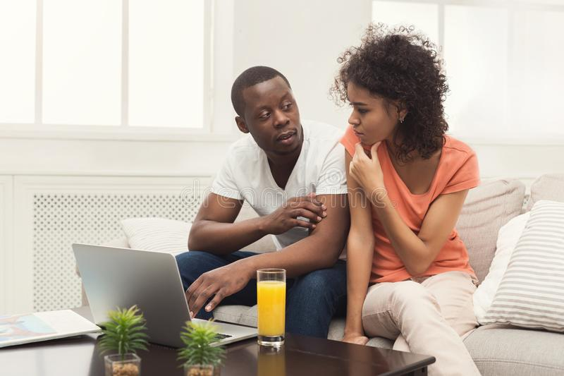 Young african-american couple working on laptop royalty free stock photo
