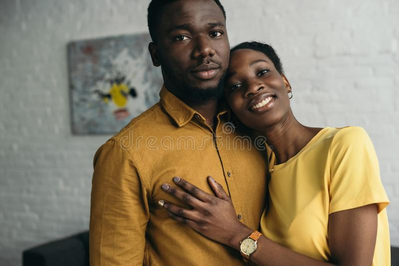 Young african american couple in yellow shirts standing together and looking at camera. At home stock photos