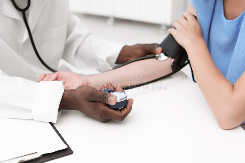 Young African-American doctor checking patient`s pulse stock photos