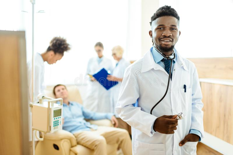 Young african-american doctor in lab coat standing with his colleagues and male patient. In the background stock photo