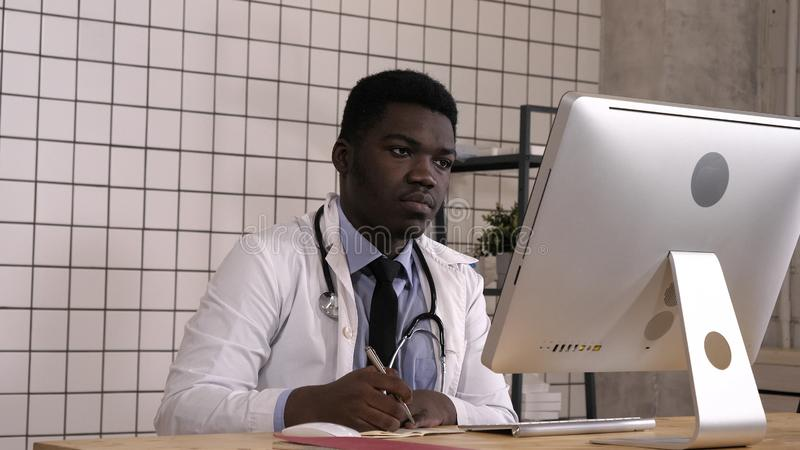 Young african-american doctor making notes and looking up something on his computer. royalty free stock photo