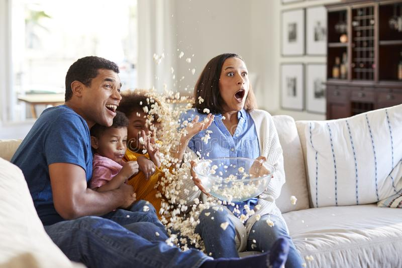 Young African American  family sitting together on the sofa in their living room watching a scary movie accidentally throwing popc royalty free stock photo