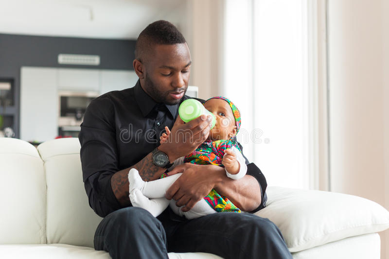 Young african american father giving milk to her baby girl in a royalty free stock photography