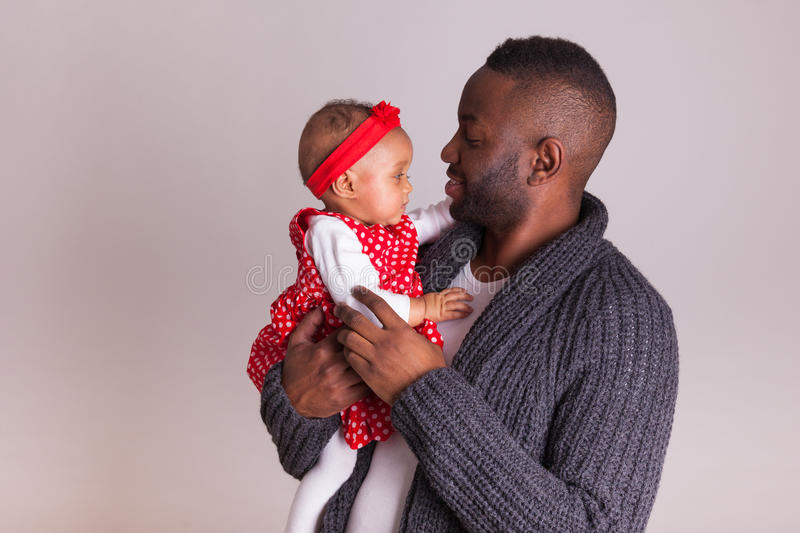 Young african american father holding with her baby girl stock images