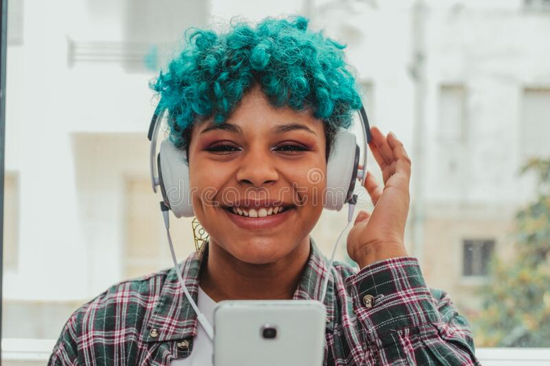 American girl with blue curl hair with mobile phone and headphones. Young african american girl with blue curl hair with mobile phone and headphones royalty free stock image