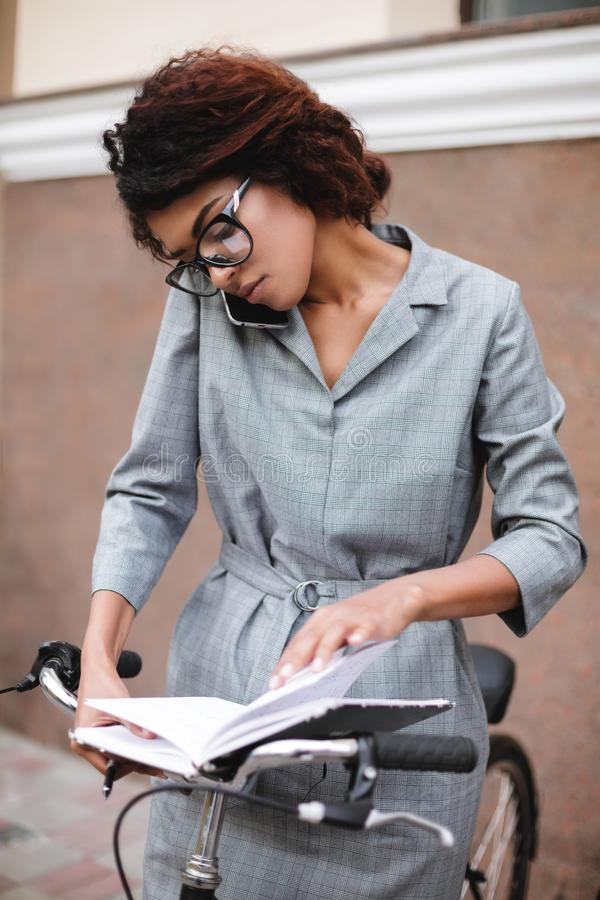 Young African American girl in glasses standing with bicycle and open notebook. Lady with dark curly hair in gray dress. Young African American girl in glasses royalty free stock photography