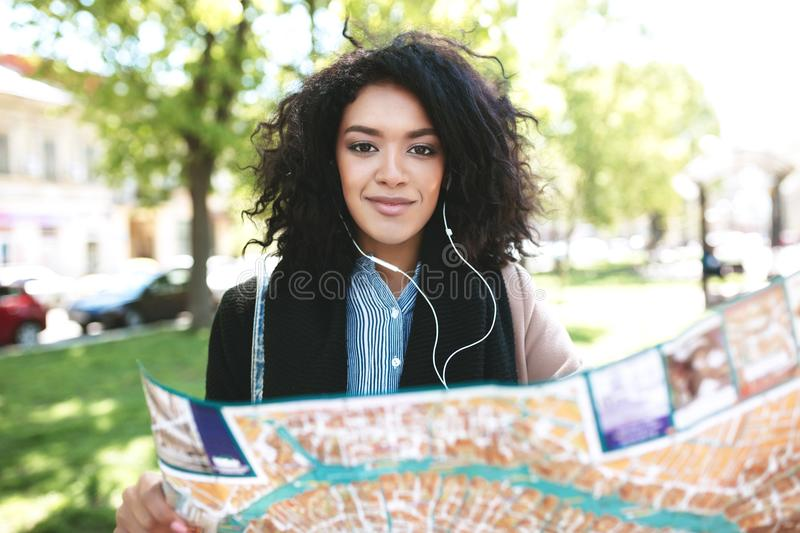 Young African American girl walking around city with map. Cheerful lady with dark curly hair looking in camera on street. Smiling girl in earphones searching royalty free stock photo