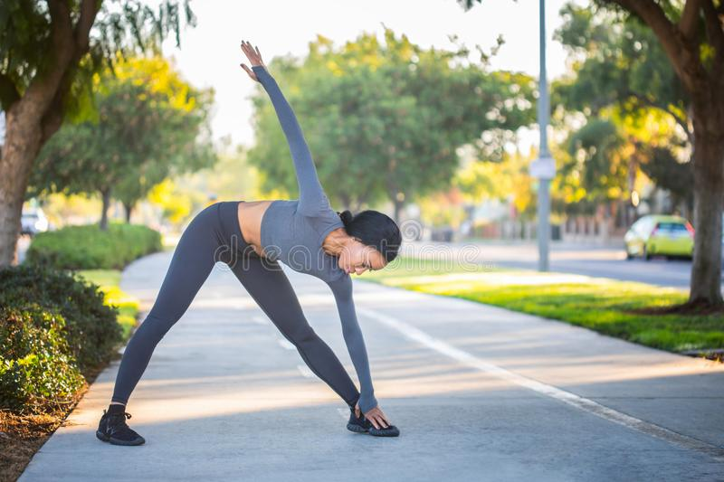 Young African American girl in workout clothes stretching on a b stock photos