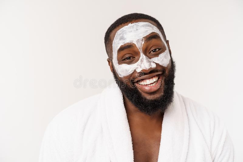 Young african-american guy applying face cream on white background. Portrait of a young happy smiling african man at royalty free stock photos