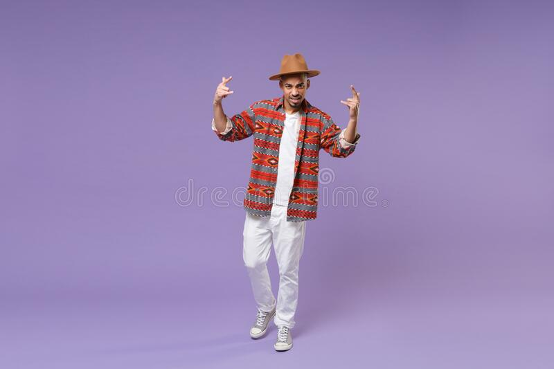 Young african american guy in casual colorful shirt hat posing isolated on violet background studio. People lifestyle stock photography