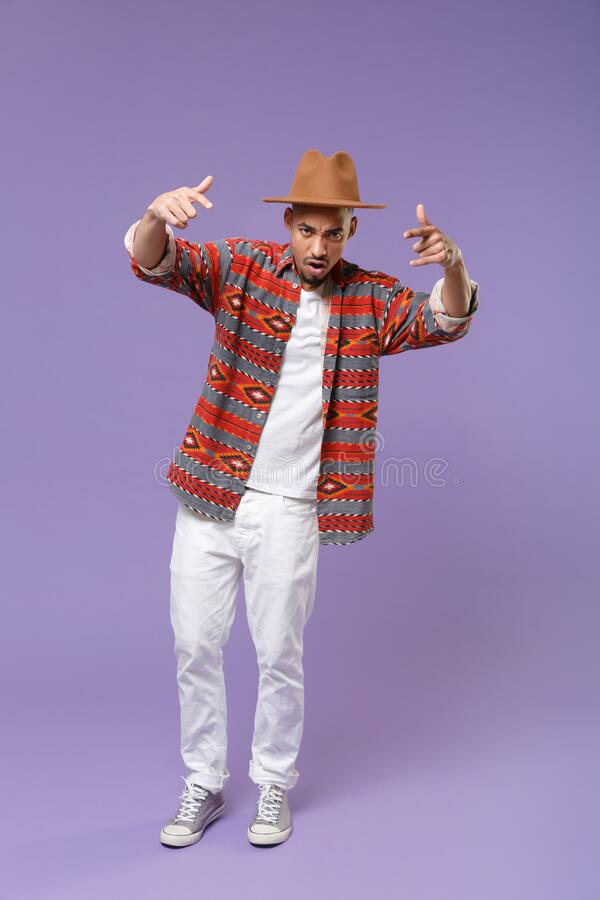 Young african american guy in casual colorful shirt hat posing isolated on violet background studio portrait. People royalty free stock photos