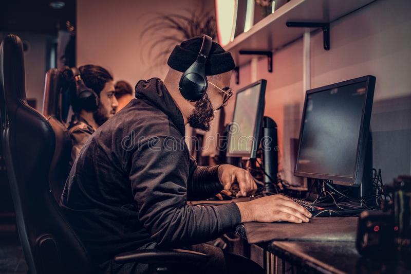 A young African American guy, enjoying spending time with his friends, playing in a multiplayer video game on a PC in a. African American guy, enjoying spending stock photography
