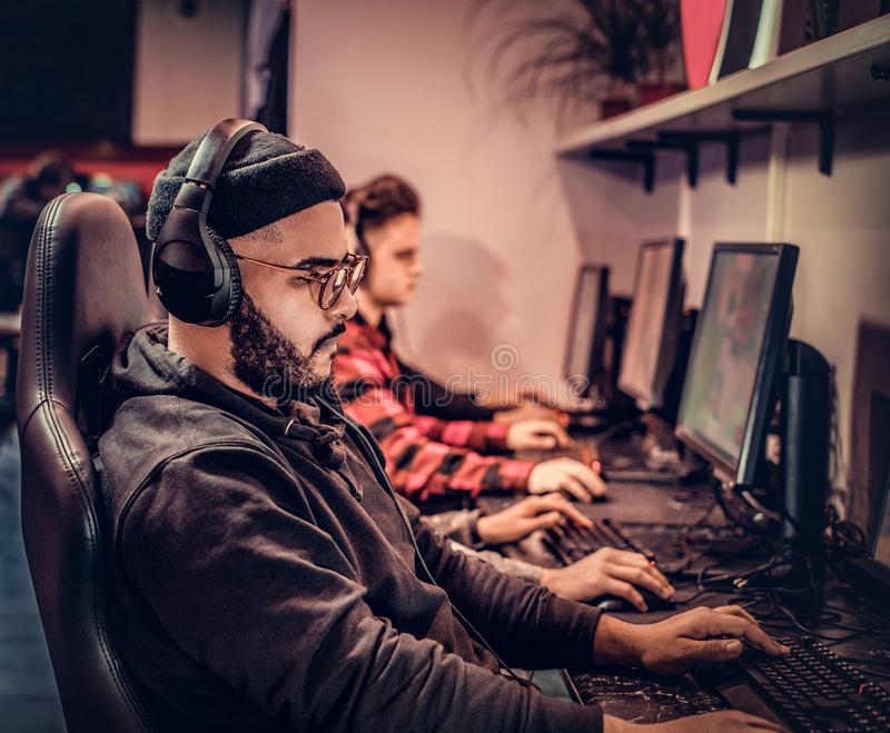 A young African American guy, enjoying spending time with his friends, playing in a multiplayer video game on a PC in a. African American guy, enjoying spending royalty free stock photos