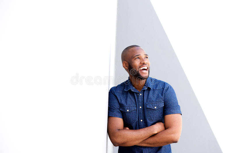 Young african american guy leaning against wall and laughing royalty free stock image