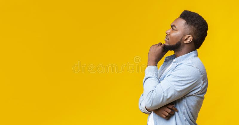 Young african american guy thinking about something over yellow background. Let me think about it. Profile portrait of thoughtful african american guy on yellow stock photography