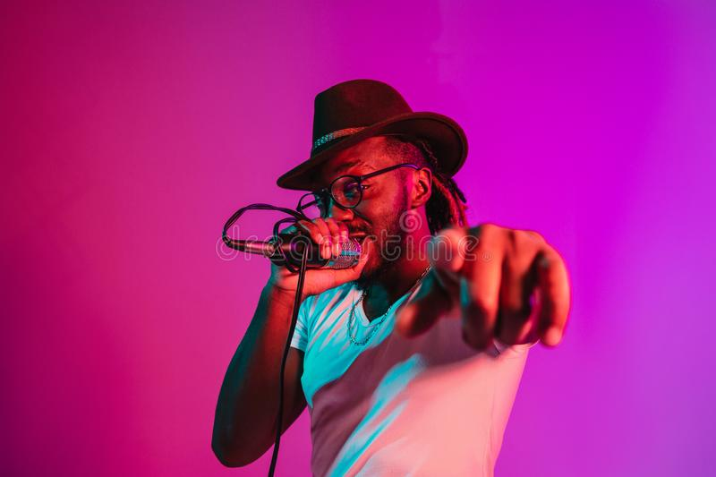 Young african-american jazz musician singing a song. Young african-american jazz musician with microphone singing a song on purple studio background in trendy royalty free stock photo