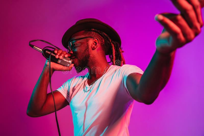 Young african-american jazz musician singing a song. Young african-american jazz musician with microphone singing a song on purple studio background in trendy stock photography