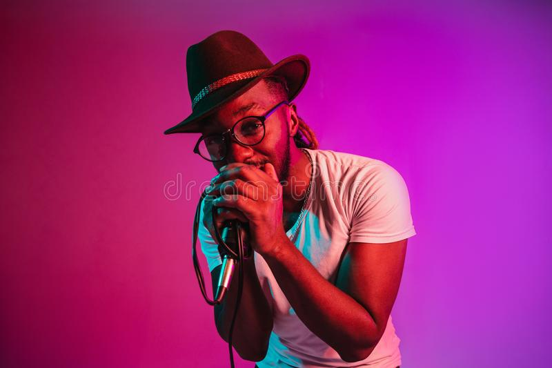 Young african-american jazz musician singing a song. Young african-american jazz musician with microphone singing a song on purple studio background in trendy royalty free stock photos