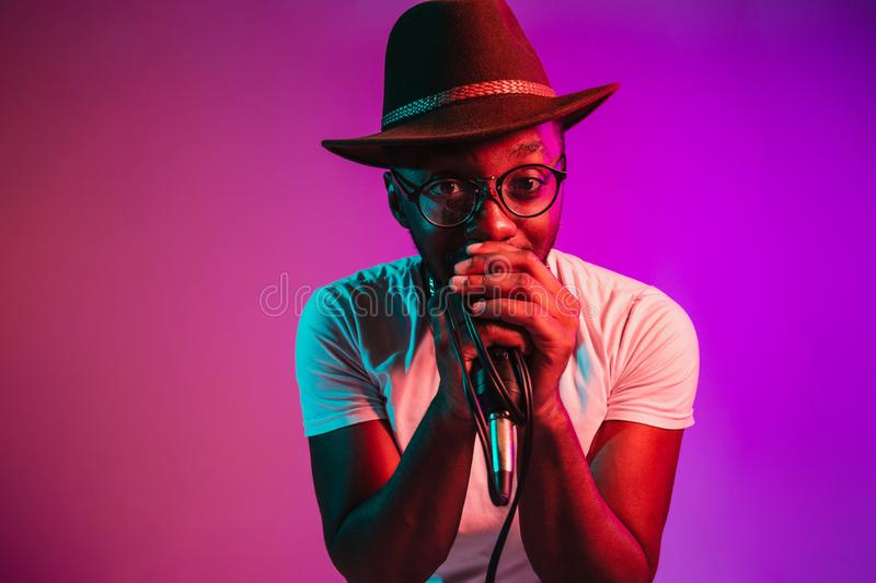 Young african-american jazz musician singing a song. Young african-american jazz musician with microphone singing a song on purple studio background in trendy royalty free stock image