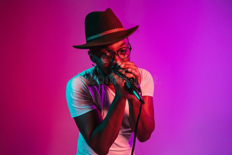 Young african-american jazz musician singing a song. Young african-american jazz musician with microphone singing a song on purple studio background in trendy stock images