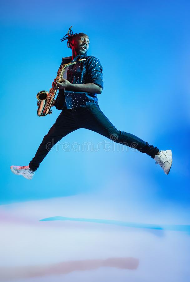 Young african-american jazz musician playing the saxophone. On blue studio background in trendy neon light. Concept of music, hobby. Joyful attractive guy royalty free stock photo