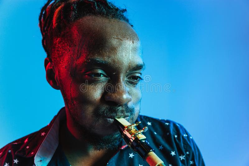 Young african-american jazz musician playing the saxophone. On blue studio background in trendy neon light. Concept of music, hobby. Joyful attractive guy stock photo