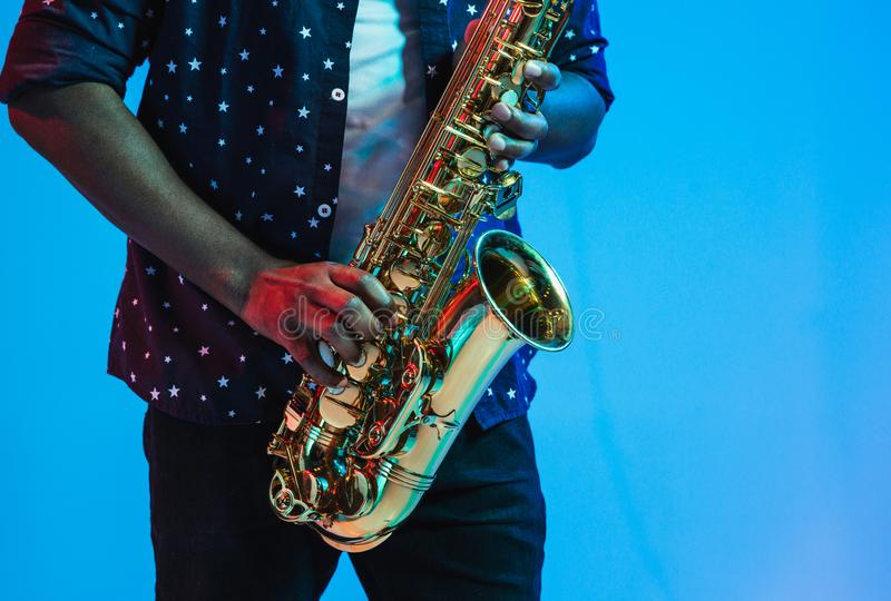 Young african-american jazz musician playing the saxophone. On blue studio background in trendy neon light. Concept of music, hobby. Joyful attractive guy royalty free stock image