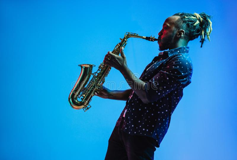 Young african-american jazz musician playing the saxophone. On blue studio background in trendy neon light. Concept of music, hobby. Joyful attractive guy royalty free stock photography