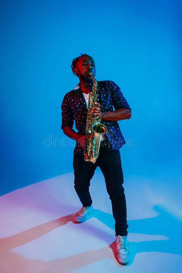 Young african-american jazz musician playing the saxophone. On blue studio background in trendy neon light. Concept of music, hobby. Joyful attractive guy stock image