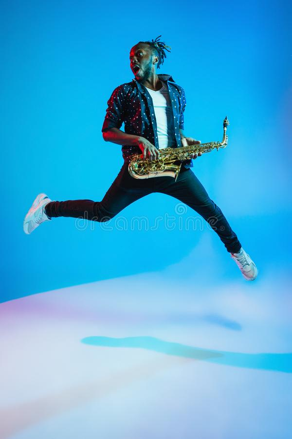 Young african-american jazz musician playing the saxophone. On blue studio background in trendy neon light. Concept of music, hobby. Joyful attractive guy stock photos