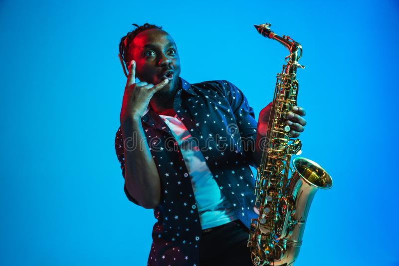 Young african-american jazz musician playing the saxophone. On blue studio background in trendy neon light. Concept of music, hobby. Joyful attractive guy stock photography