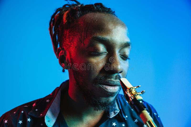 Young african-american jazz musician playing the saxophone. On blue studio background in trendy neon light. Concept of music, hobby. Joyful attractive guy stock images