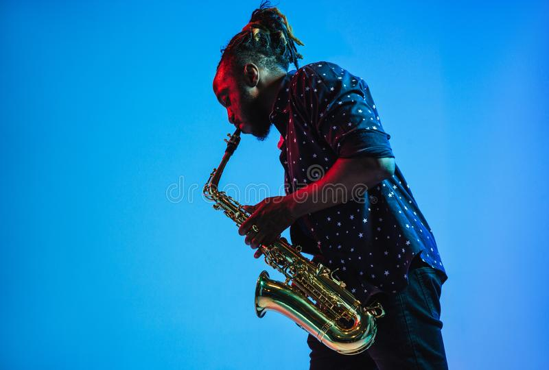 Young african-american jazz musician playing the saxophone. On blue studio background in trendy neon light. Concept of music, hobby. Joyful attractive guy royalty free stock photos