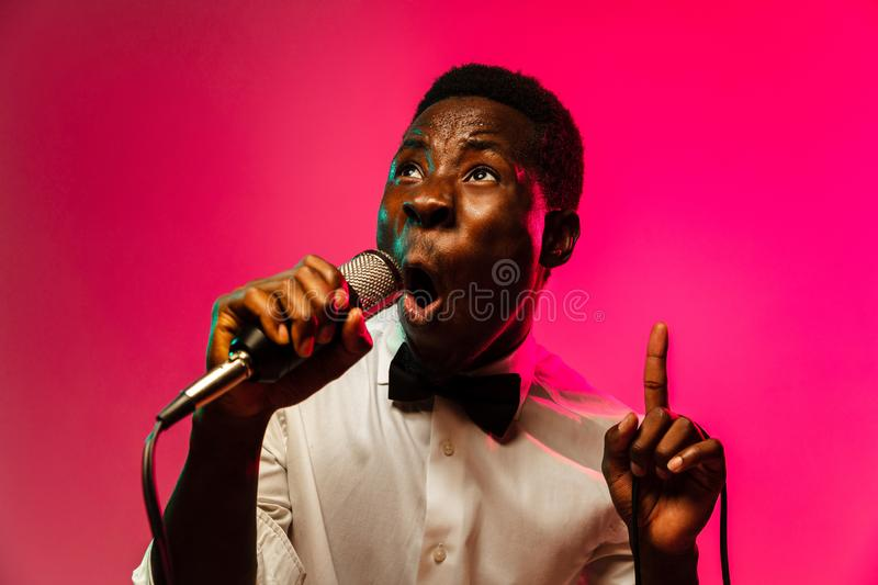 Young african-american jazz musician singing a song. On gradient pink-red background in neon light. Concept of music, hobby, festival, open-air. Joyful guy royalty free stock images