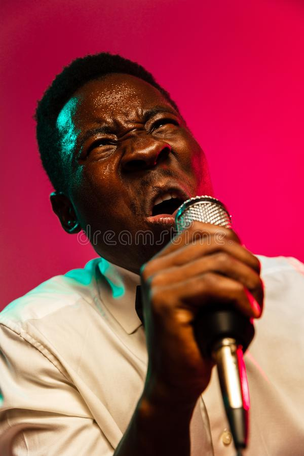 Young african-american jazz musician singing a song. On gradient pink-red background in neon light. Concept of music, hobby, festival, open-air. Joyful guy stock images