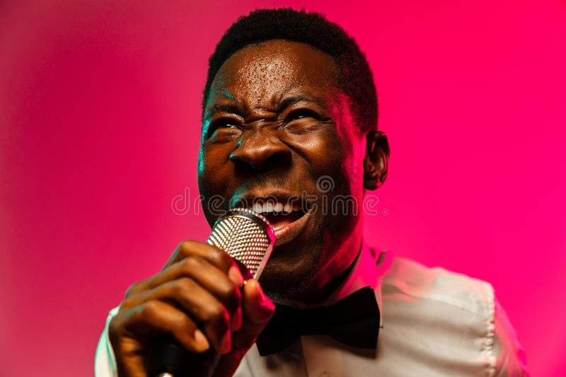 Young african-american jazz musician singing a song. On gradient pink-red background in neon light. Concept of music, hobby, festival, open-air. Joyful guy royalty free stock image
