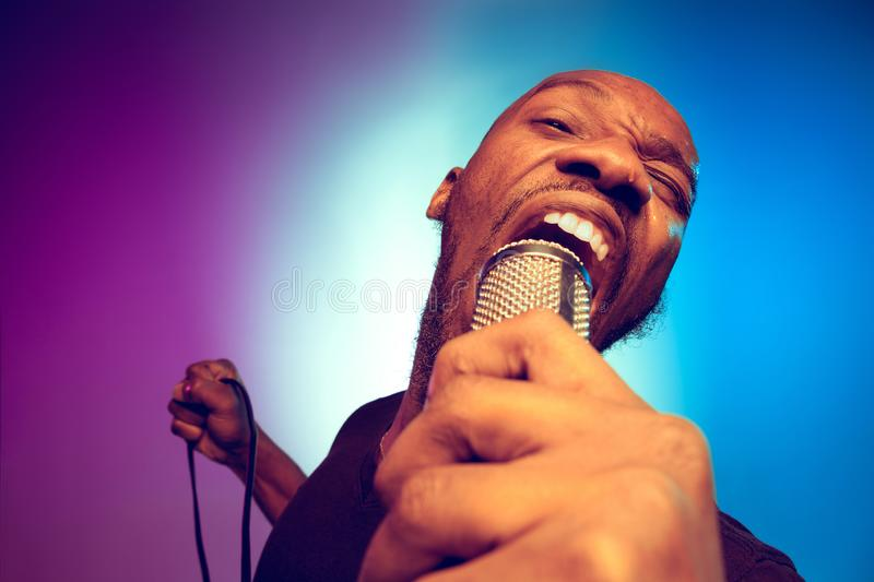Young african-american jazz musician singing a song. On gradient purple-blue background. Concept of music, hobby. Joyful attractive guy improvising, having a royalty free stock image