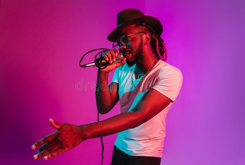 Young african-american jazz musician singing a song. Young african-american jazz musician with microphone singing a song on purple studio background in trendy stock photo