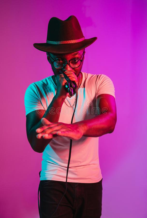 Young african-american jazz musician singing a song. Young african-american jazz musician with microphone singing a song on purple studio background in trendy stock photos