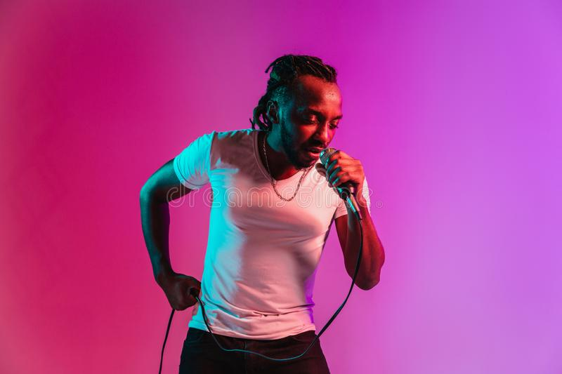 Young african-american jazz musician singing a song. Young african-american jazz musician with microphone singing a song on purple studio background in trendy royalty free stock photography