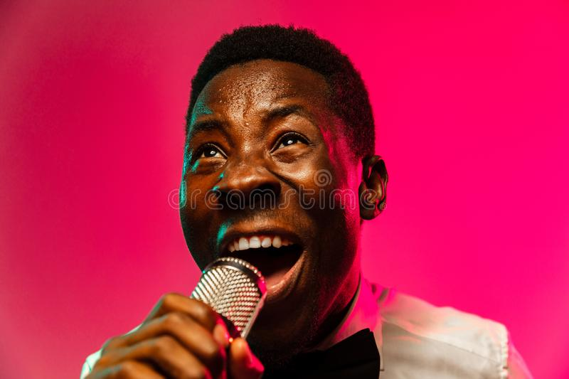Young african-american jazz musician singing a song. On gradient pink-red background in neon light. Concept of music, hobby, festival, open-air. Joyful guy stock photo