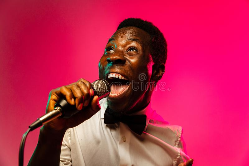 Young african-american jazz musician singing a song. On gradient pink-red background in neon light. Concept of music, hobby, festival, open-air. Joyful guy stock image