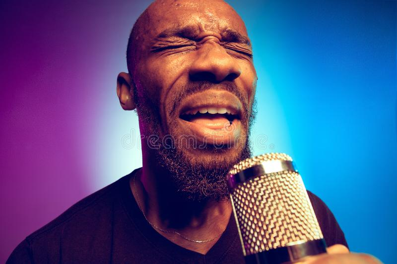 Young african-american jazz musician singing a song. On gradient purple-blue background. Concept of music, hobby. Joyful attractive guy improvising, having a royalty free stock photo