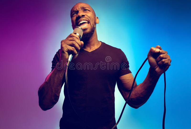 Young african-american jazz musician singing a song. On gradient purple-blue background. Concept of music, hobby. Joyful attractive guy improvising, having a stock photos
