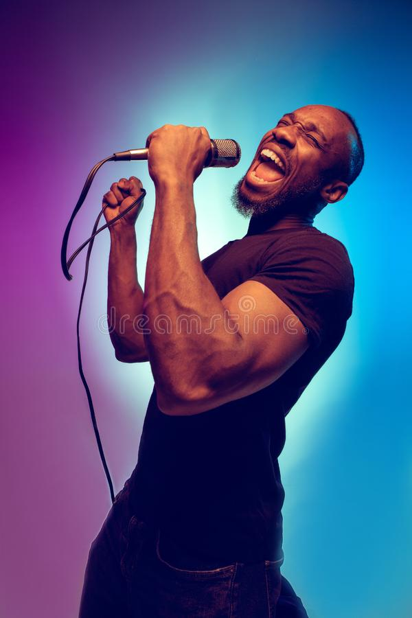Young african-american jazz musician singing a song. On gradient purple-blue background. Concept of music, hobby. Joyful attractive guy improvising, having a stock photography
