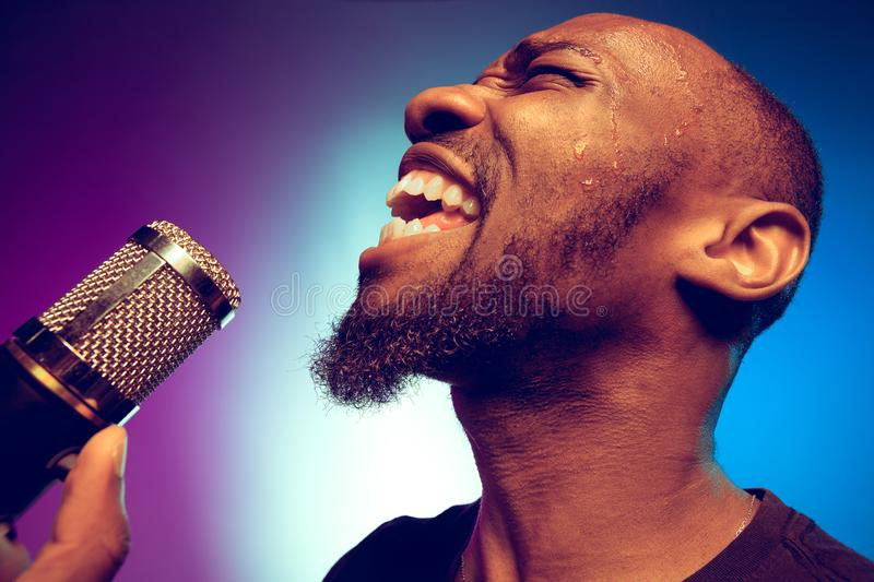 Young african-american jazz musician singing a song. On gradient purple-blue background. Concept of music, hobby. Joyful attractive guy improvising, having a royalty free stock photography